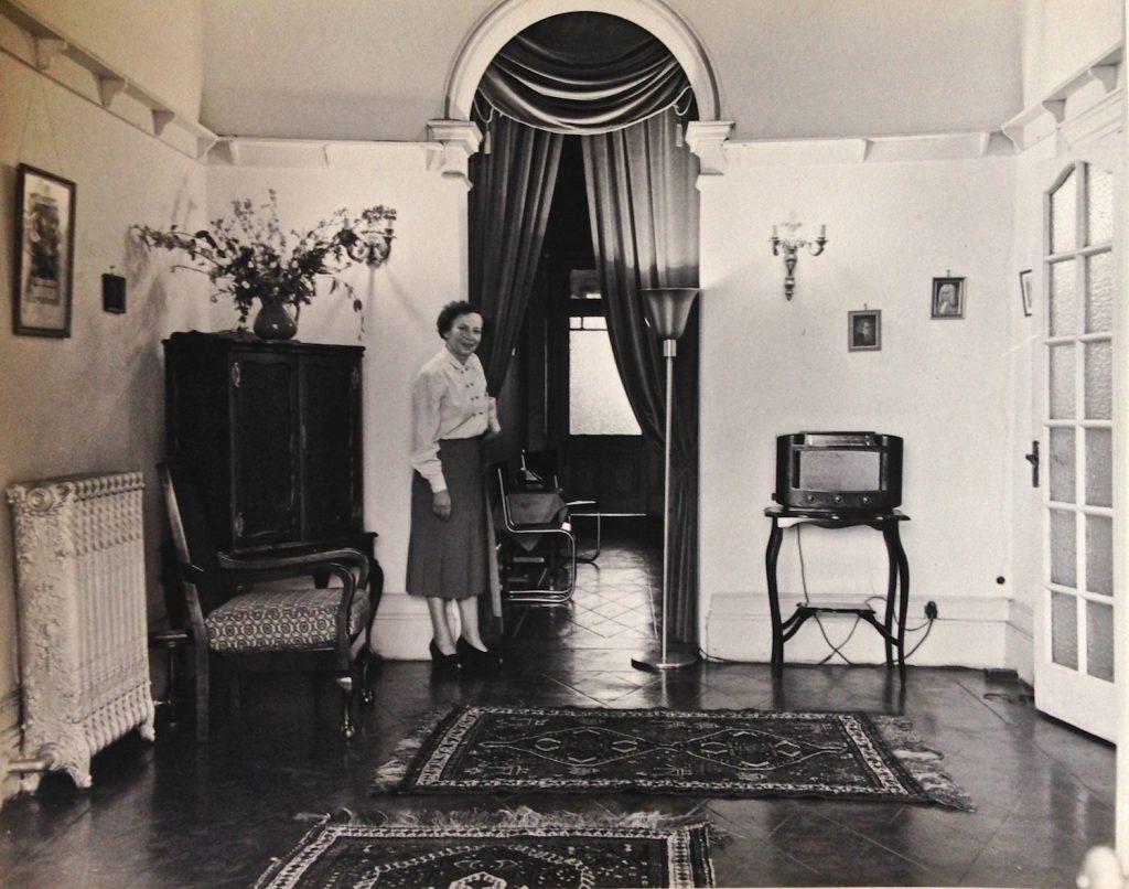 Mrs Prager in the house's original entrance hall [photo courtesy of Twilsharp Studios]