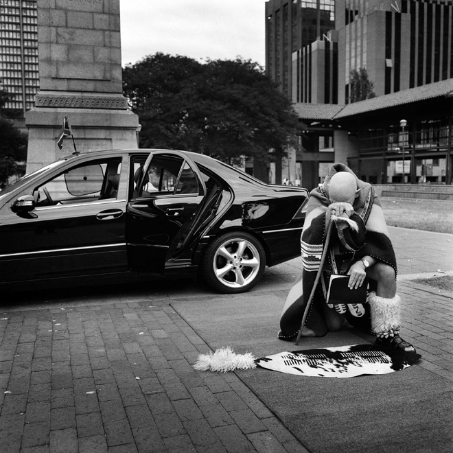 A black man in tribal attire kneeling on the ground with his head bowed; a black Mercedes is behind him